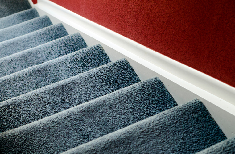 Blue-grey carpet on the stairs leading to the second floor of a house